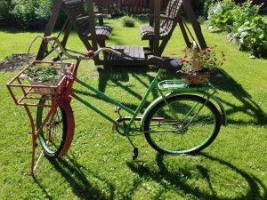 puutarhakeinun edessä on vihreä pyörä, jonka päällä on kaksi kukkakoria