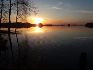 auringonlasku veden äärellä
